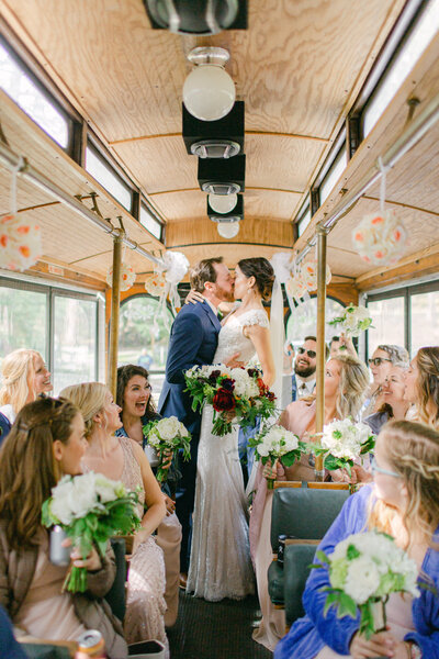 Bride and groom kiss on trolley while wedding party looks on full of joy and laughter
