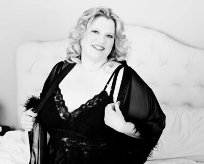 black and white photo of a blonde curvy woman in black lingerie posing for boudoir photos at Boudoir & Pinup by Janet Lynn Photography