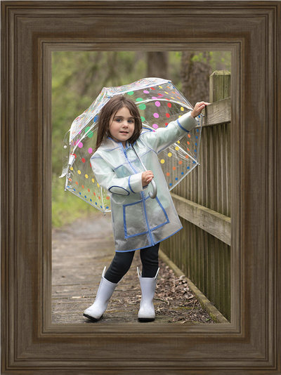Little Girl on bridge in raincoat holding an umbrella