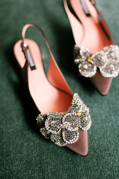 pink velvet shoes with diamond embellishments styled on vibrant green carpet at the brown hotel