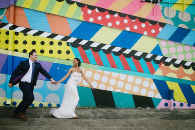 Bride and Groom are running in front of a colorful mural in Nashville and smiling at eachother