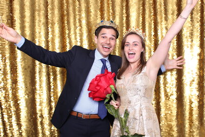 couple posing in front of the gold sequin backdrop of a photo booth at the vinoy renaissance in st petersburg, fl