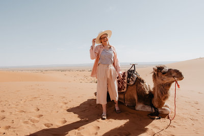 woman standing in desert with camel
