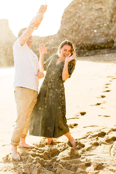 Engaged couple popping champagne in Malibu, California. Photo taken by Cheers Babe Photo.