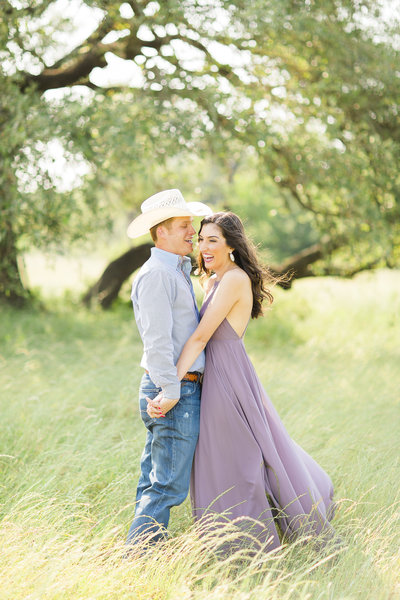 film photograph of engaged couple in a field
