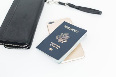 USA passport with gold iphone and a black wallet