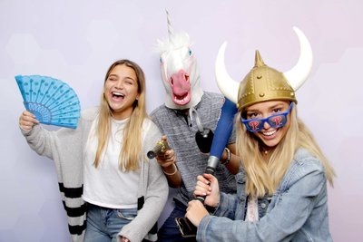 girls having a blast while posing with a unicorn mask