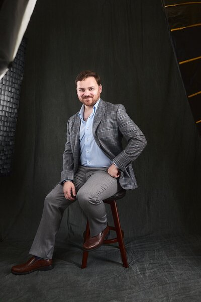 Atlanta studio portrait of male sitting on stool in suit
