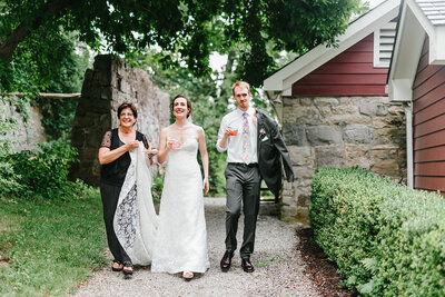 Katherine, of Crossed Keys Estate staff, escorts bride and groom down outdoor path