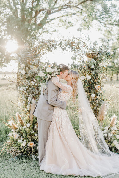 A gorgeous bride and groom kissing in front of a floral installation