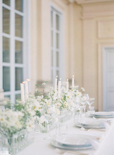 Reception table on veranda of Villa Cimena in Turin Italy. Table has all with linens, tableware, flowers and candles. Water and wine glasses are all clear. Villa is a cream color with pale blue doors and windows. Photographed by destination wedding photographers Amy Mulder Photography.
