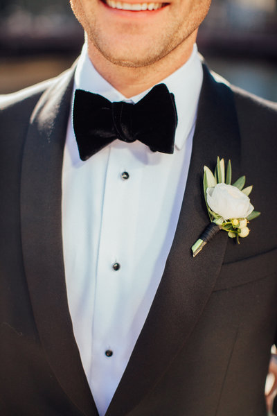 Groom wearing white ranunculus boutonniere