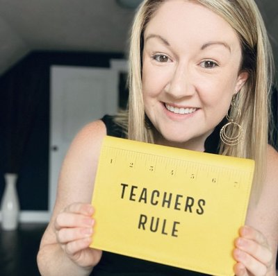 A teacher shows a yellow notebook that says  Teachers Rule with a picture of a ruler.