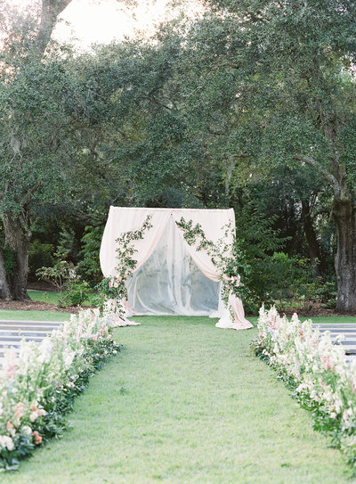 Wedding Ceremony Inspirtation Blush Draped Arbor with Climbing Greenery and Floral Lined Aisle at RiverOaks Charleston