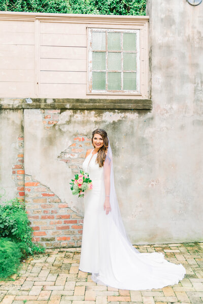 Brunette bride in keyhole neck white sating wedding gown and floor length white veil holding bouquet of pink roses, baby's breath, and greenery while standing in front of aged concrete and red brick wall taken by New Orleans wedding photographer Elizabeth Collins
