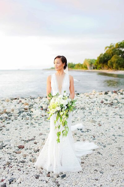 Bride posing with floral bouquet at Olowalu