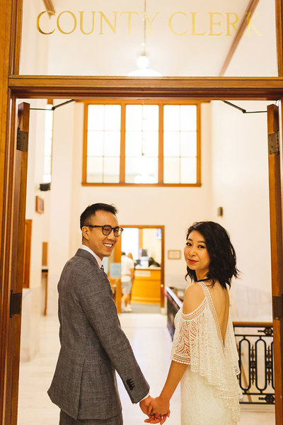 couple standing under the City Clerk sign in the doorway at SF city hall by SF City Hall wedding photographer Zoe Larkin Photography