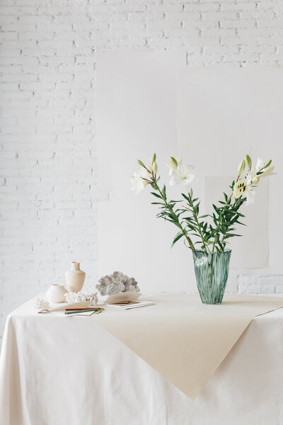 flowers sitting on table with white table cloth