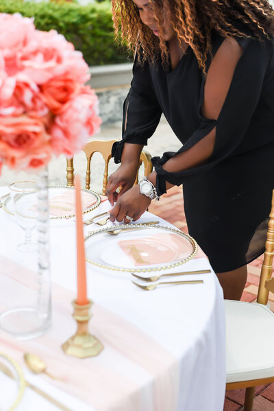 "alt=""tamp wedding planner setting up table decor"""