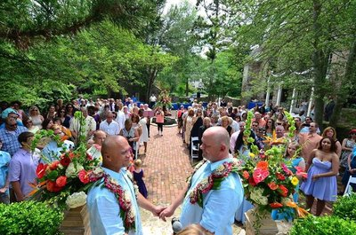 Two grooms holding hands and smiling at each other during their wedding at Holly Hedge Estate. Officiated by wedding officiant Donna Forsythe of Lehigh Valley Celebrants.