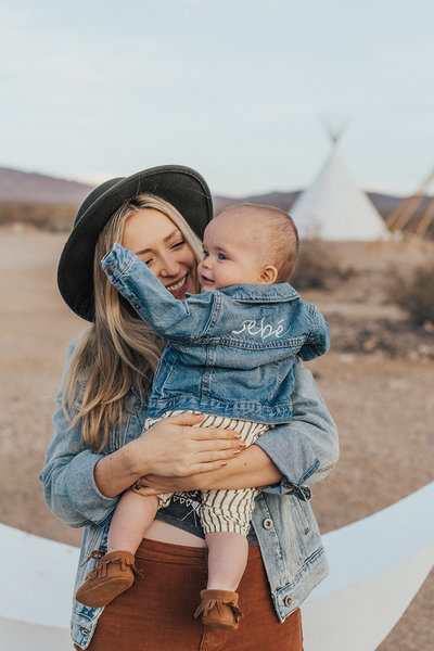 woman holding baby wearing embroidered jean jacket