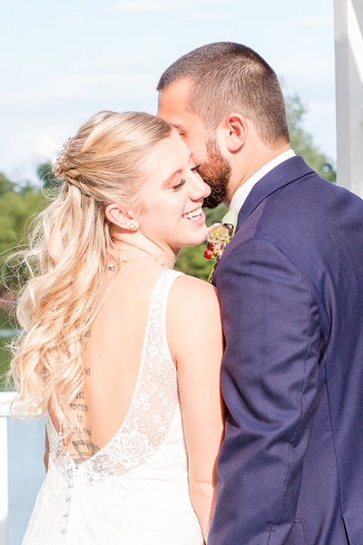 Groom whispers secret in his beautiful bride's ear as she smiles on their wedding day