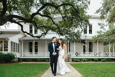 bride and groom walking in front of white two stories house austin Mattie's