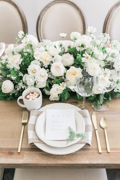 a christmas dinner place setting with gold flatware, white florals, lyme check napkins and gold flatware