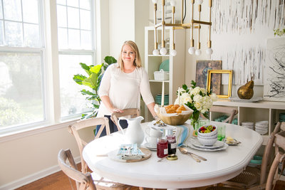 Interior designer stages a dining table and smiles during brand photography session
