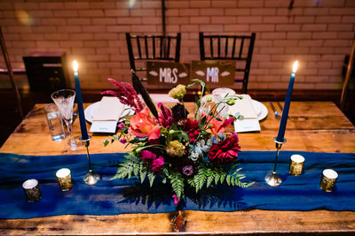 Wedding Reception head table with floral arrangement bouquet and blue runner