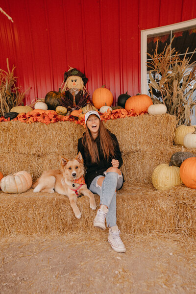 woman laughing with her dog beside her in a pumpkin patch