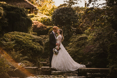 Bride and Groom kissing stood on steeping stones over water at Compton Acres
