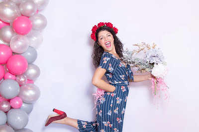 stylish girl posing front of a photo booth with balloons, confetti and flowers.