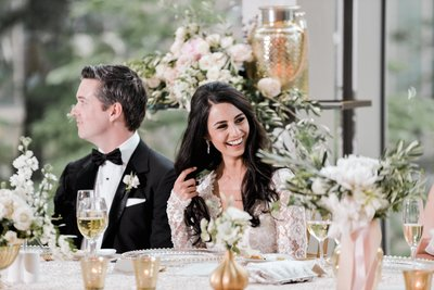 Laughing bride and groom at the Royal Conservatory of Music with green and pink flowers