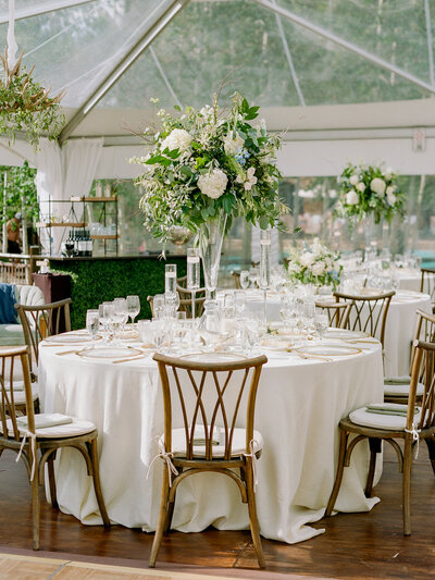 Wedding reception table with white table cloth, tall bouquets of large white flowers and green foliage