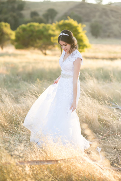brunette bride with classic makeup updo and a white dress in a field in San Jose, California