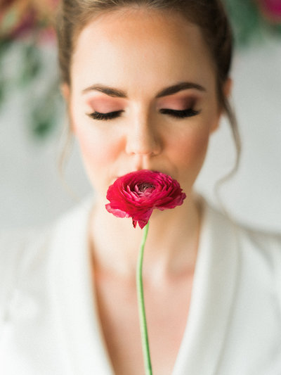 bride getting ready for wedding smelling a flower