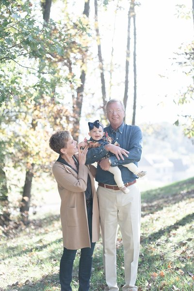 Two grandparents are standing outside in the Fall and holding their granddaughter in Brentwood Tennessee