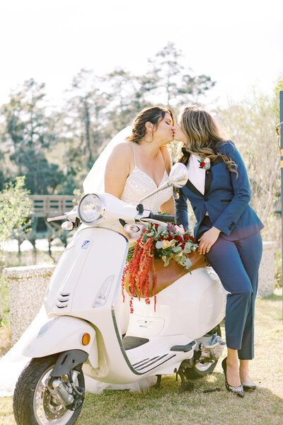 Romantic euro-inspired lesbian wedding couple, two brides, kissing over a moped at the Wyld Dock Bar in Savannah