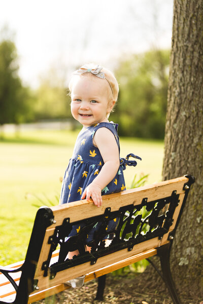 toddler girl smiling for portrait on bench in ohio