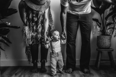 mom and dad holding hands of toddler with suspenders