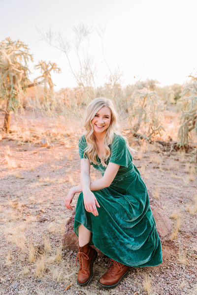 blonde high school  senior in field wearing green velvet dress
