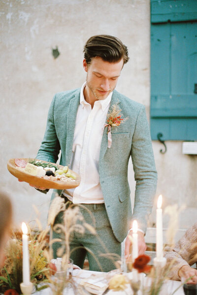 Groom in a sage green ASOS suit during his family style wedding dinner
