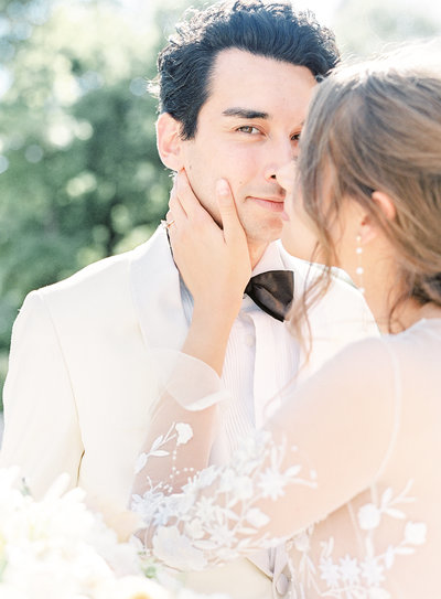 Groom looking in to camera while the bride is nuzzling her nose in to his with her hand lightly on his jawbone. He is in a white dinner jacket and black bow tie. Photographed at a destination wedding in France by wedding photographers in  Charleston Amy Mulder Photography