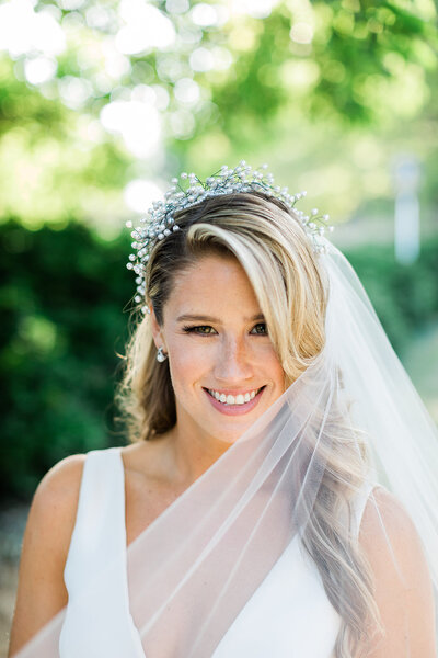 Bride Wearing Flower Crown and Veil smiles at camera
