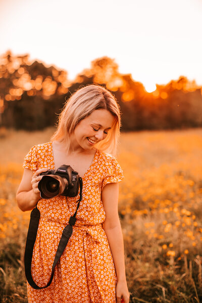main photographer in a field with camera and sunset