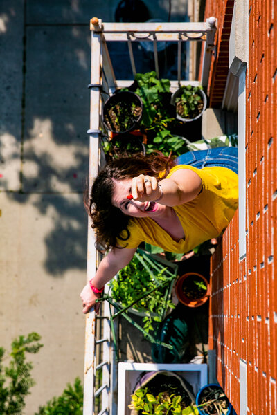 Woman happily gardening on her small balcony