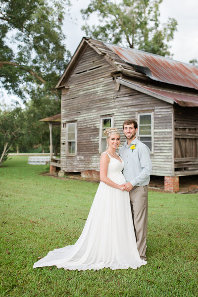 bride and groom standing in front of an old barn in savannah georgia