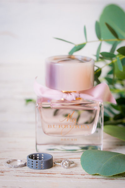 A stunning Burberry perfume bottle with wedding rings in front.