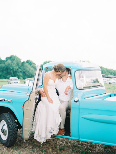 bride and groom share a kiss in an old classic blue chevy truck,photography by Grand Rapids wedding photographer Cynthia Boyle